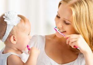 mother and baby brushing teeth together