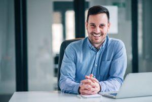 Man sitting at his desk smiling