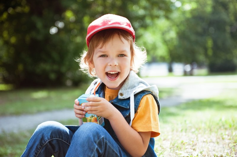 a child sitting outside and drinking a juice box